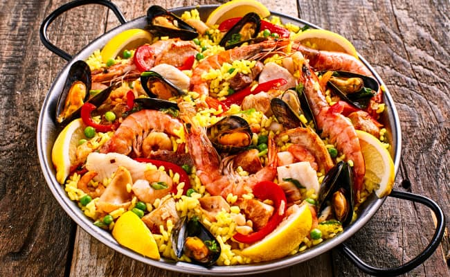 paella for two with shrimp, calamari, mussels, clams, octopus, spanish chorizo, merguez sausage, paquillo peppers, english peas, saffron rice, lemon