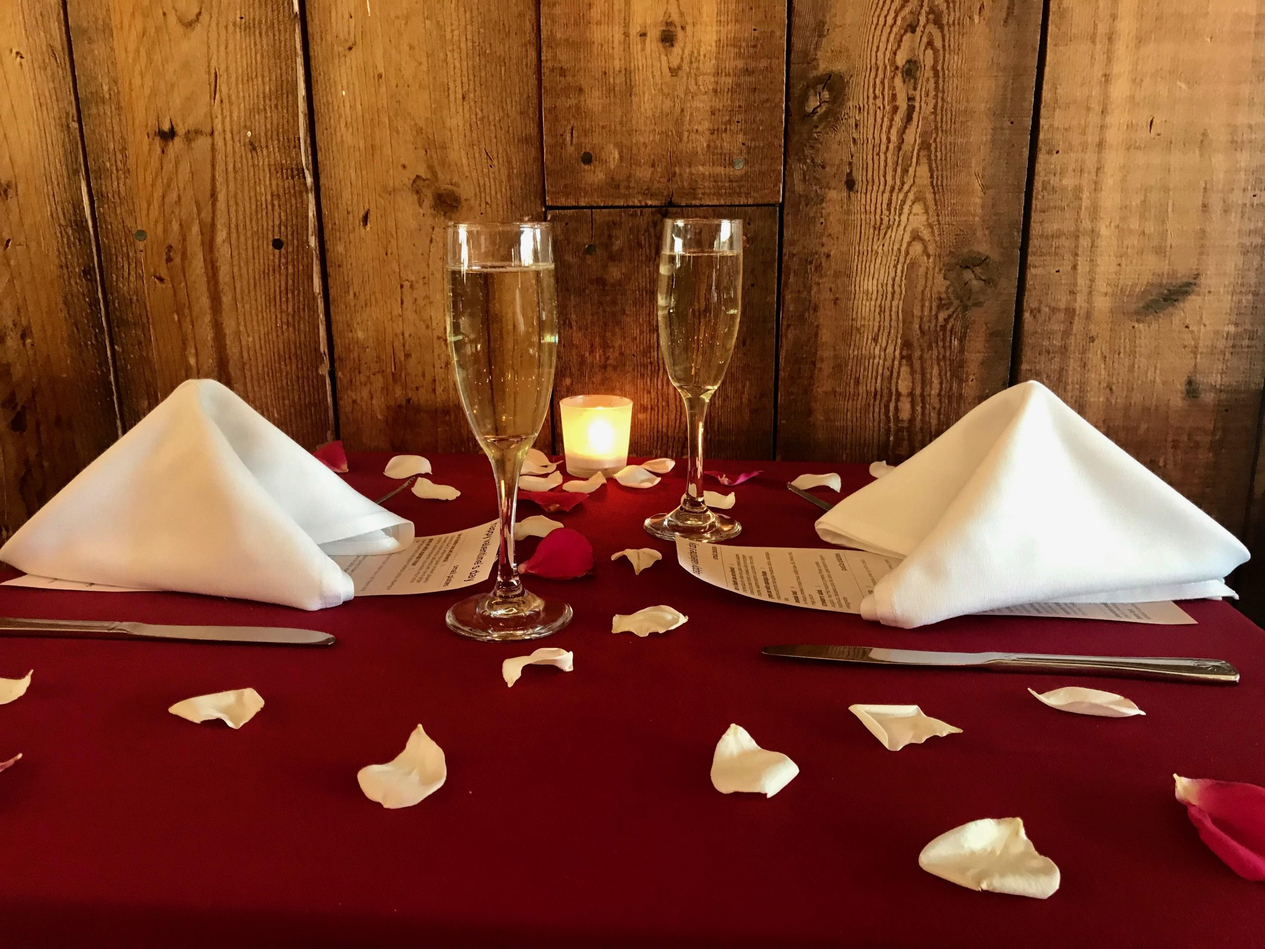 valentines table with rose petals, champagne glasses, and white linen napkins folded