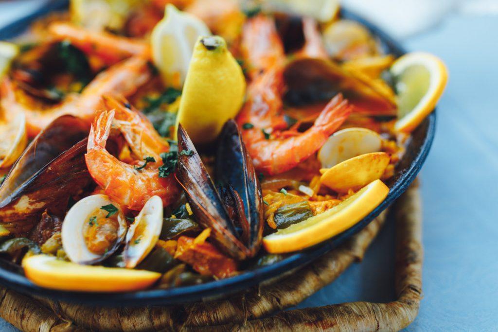 paella with mixed shellfish, shrimp, rice, lemon
