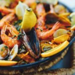 paella with mixed shellfish, shrimp, rice, lemon